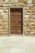 elegant wooden door and stone wall, detail of facade in Florence