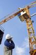 building engineer directing large construction crane