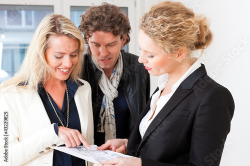 Young realtor explaining ground plan to couple