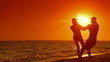 Young Couple Spinning On The Beach at Sunset