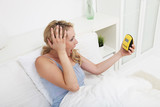 Woman looking at alarm clock in horror