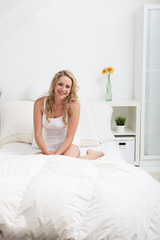 Friendly blonde woman sitting on her bed in a bedroom interior