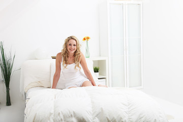 Woman relaxing on her bed in a modern bedroom interior