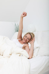 Woman stretching with her arm raised against her pillows