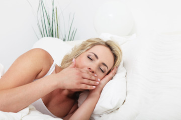 Young woman lying in her comfortable bed yawning