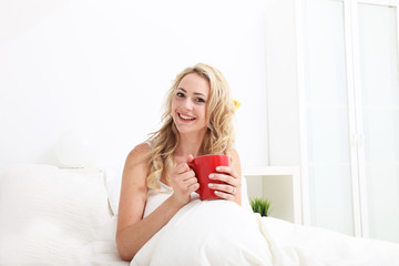 Friendly woman with beautiful smile in bed