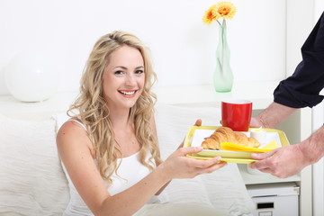 Young woman being treated to breakfast in bed