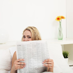 Young woman reading morning newspaper