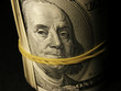 Money roll with US dollars with Benjamin Franklin portrait.