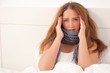 Junge Frau liegt krank im Bett
