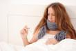 Junge kranke Frau mit Fieberthermometer