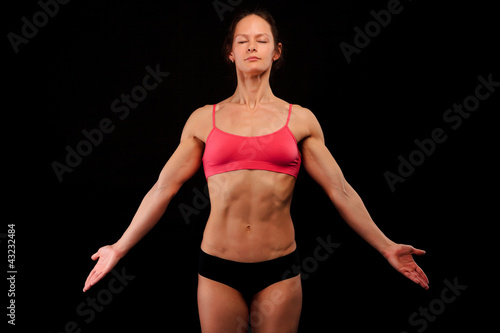 Muscular woman on black background.