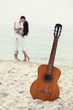 Couple kissing at the beach and guitar.