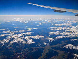 air plane wing and blue sky over the Alps