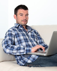 man on sofa with computer