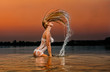 sexy blonde woman in water at sunset .Beautiful swimsuit model