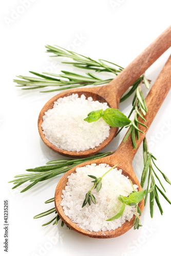 salt in spoons with fresh basil, thyme and rosemary isolated