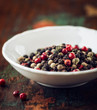 Different types of peppercorns in a small bowl