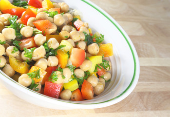Chick pea salad in a bowl sitting on a wooden table.