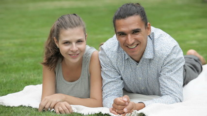 young girl and guy lying on the meadow smiling