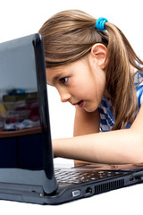 Cute little girl is sitting  with her laptop