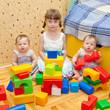 preschooler and two twins baby building of blocks