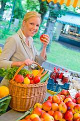 Frau am Obstmarkt mit Einkaufskorb