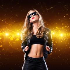 junge blonde Frau im Rocker-Outfit vor Lichterhintergrund