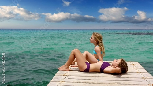beautiful girls tanning in ibiza island in mediterranean sea