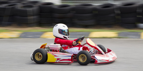 Young asian boy racing in a go kart