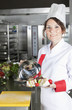 portrait of mid adult female chef in kitchen presenting dish