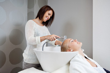 Beautician Washing Hair Of Customer