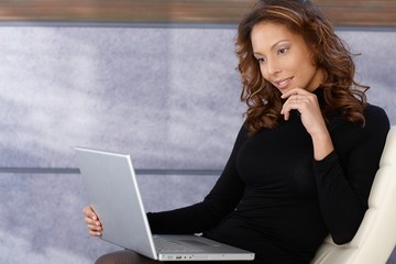 Beautiful ethnic female using laptop computer