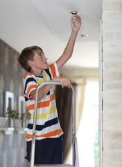 Boy does homework replaces a light bulb