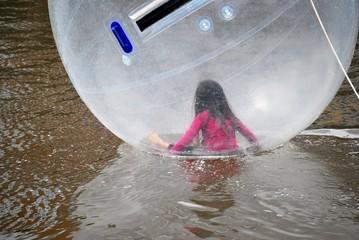 Kleines Mädchen in einem Water waling ball