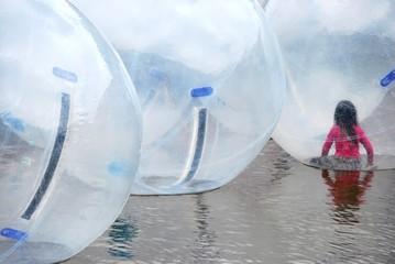 Kleines Mädchen und Water walking balls