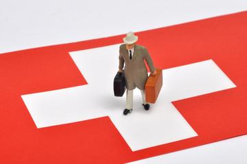 Geschäftsmann mit Koffern auf Schweizer Fahne