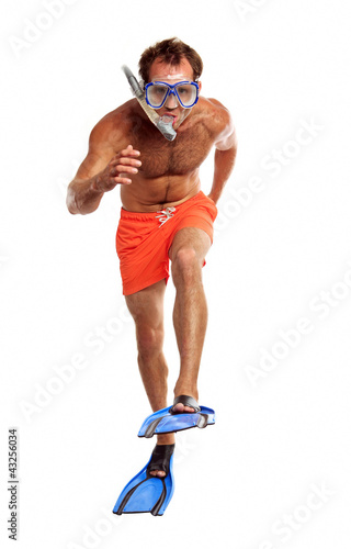 Caucasian swimmer wearing mask, snorkel and flippers walking