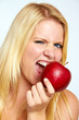 beautiful young blond smiling girl eating an red apple