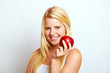 beautiful young blond smiling girl eating red apple