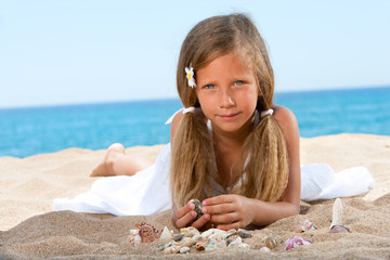 Sweet girl playing with shells on beach.