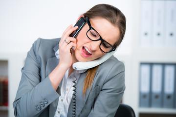 geschäftsfrau führt zwei telefonate gleichzeitig