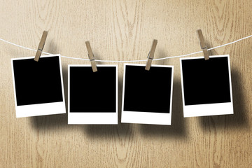 four photo paper attach to rope on wooden background