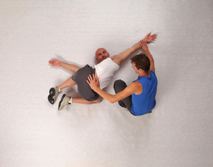 muscular man stretching with personal trainer in studio