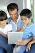 Father and kids websurfing on digital tablet
