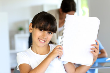 Closeup of beautiful school girl showing notebook page