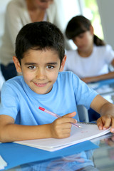 Portrait of smilng young boy sitting in classroom