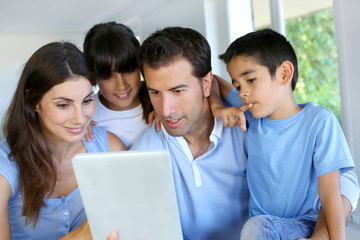 Parents and children using electronic tablet at home