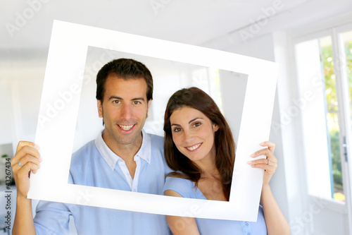 Closeup of cheerful couple looking through frame