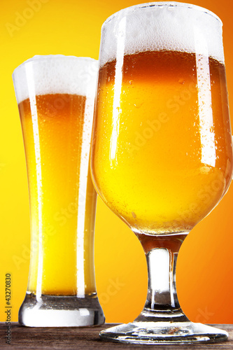 Beer into glass on golden background